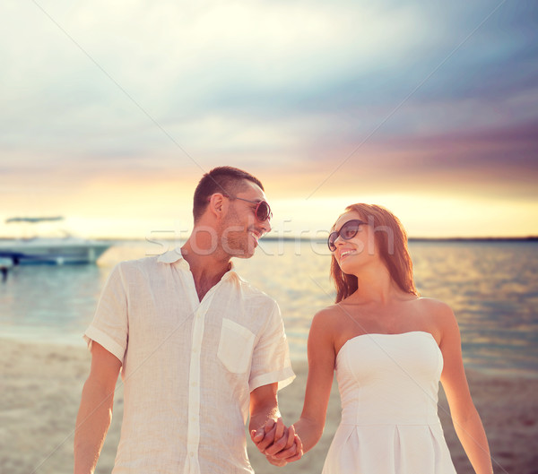 Smiling Couple In Sunglasses Walking On Beach Stock Photo