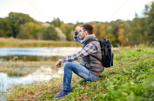 smiling man with backpack resting on river bank Stock photo © dolgachov