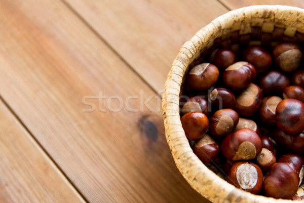 close up of chestnuts in basket on wooden table Stock photo © dolgachov