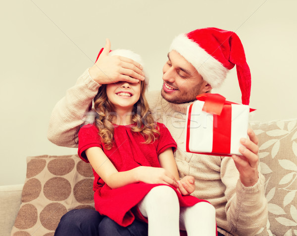 smiling father surprises daughter with gift box Stock photo © dolgachov
