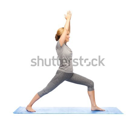 woman making yoga warrior pose on mat Stock photo © dolgachov