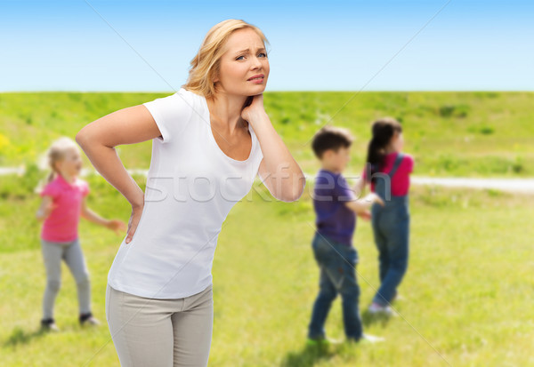 woman suffering from backache over group of kids Stock photo © dolgachov