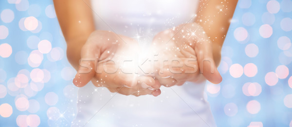 magic twinkles or fairy dust on female hands Stock photo © dolgachov