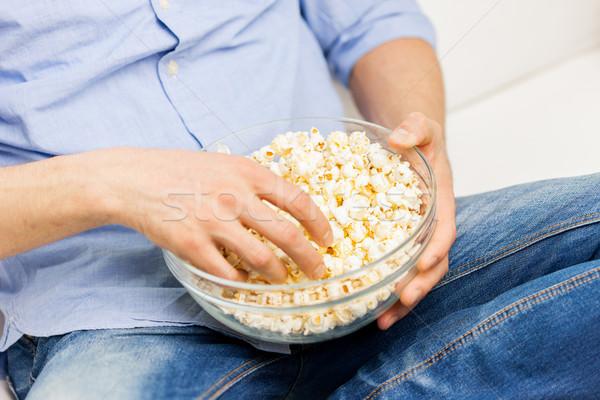 Adam yeme patlamış mısır ev gıda Stok fotoğraf © dolgachov