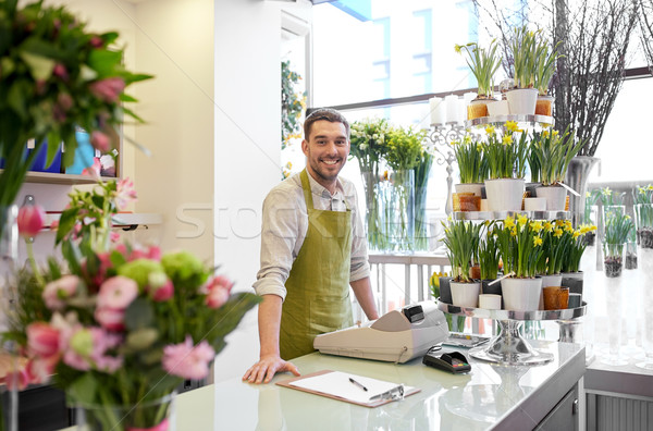 florist man with clipboard at flower shop counter Stock photo © dolgachov
