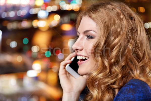 young woman with smartphone at night club or bar Stock photo © dolgachov