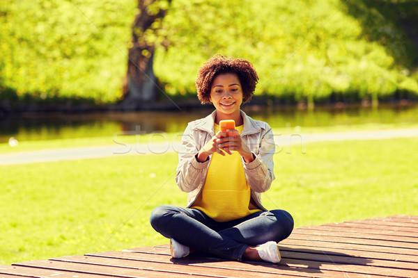 Gelukkig afrikaanse jonge vrouw messaging smartphone technologie Stockfoto © dolgachov
