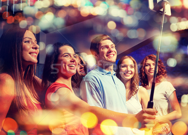 friends with smartphone taking selfie in nightclub Stock photo © dolgachov
