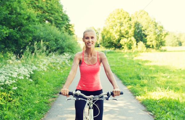 Szczęśliwy młoda kobieta jazda konna rower odkryty fitness Zdjęcia stock © dolgachov