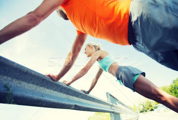 close up of happy couple doing push-ups outdoors Stock photo © dolgachov