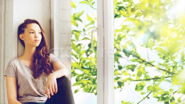 sad pretty teenage girl sitting on windowsill Stock photo © dolgachov