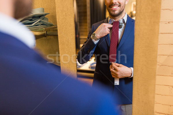 close up of man trying tie on at mirror Stock photo © dolgachov