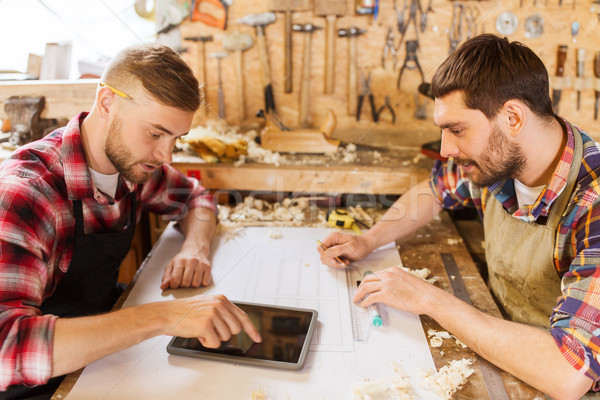 workmen with tablet pc and blueprint at workshop Stock photo © dolgachov