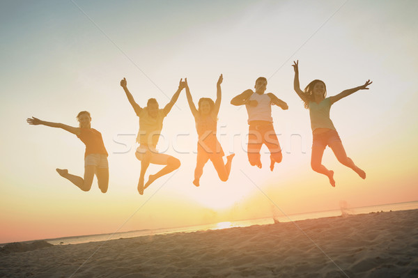 smiling friends dancing and jumping on beach Stock photo © dolgachov