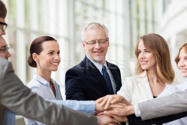üzletemberek kezek felső iroda csapatmunka mosolyog Stock fotó © dolgachov