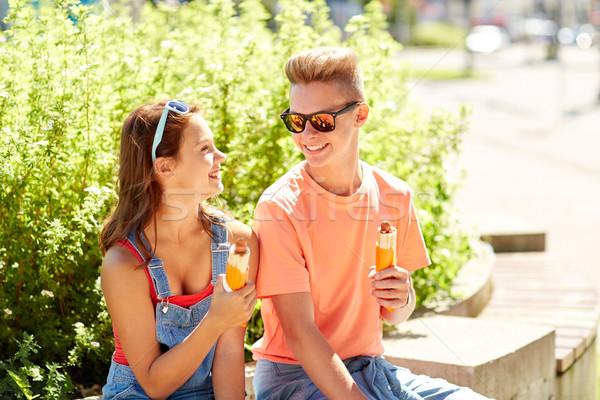 Feliz adolescente casal alimentação quente cães Foto stock © dolgachov
