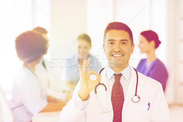 happy doctor over group of medics at hospital Stock photo © dolgachov