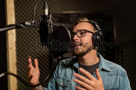 man with headphones singing at recording studio Stock photo © dolgachov