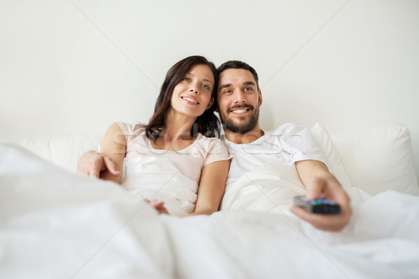 happy couple lying in bed at home and watching tv Stock photo © dolgachov