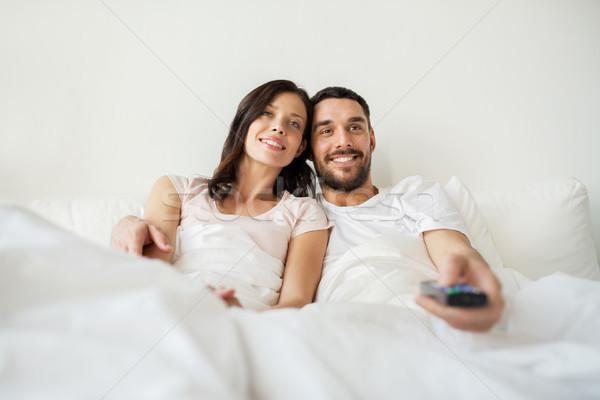 Szczęśliwy para bed domu oglądania telewizja Zdjęcia stock © dolgachov