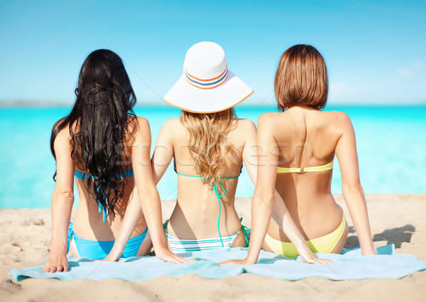 group of women in swimwear sunbathing on beach Stock photo © dolgachov