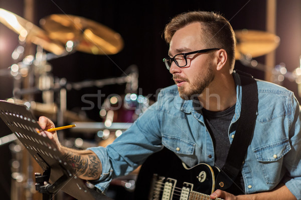 man with guitar writing to music book at studio Stock photo © dolgachov