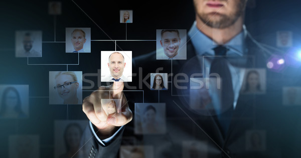 Stock photo: businessman touching virtual screen with contacts