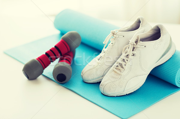 close up of sneakers, dumbbells and sports mat Stock photo © dolgachov