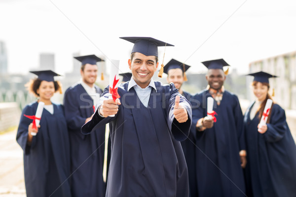 happy students with diplomas showing thumbs up Stock photo © dolgachov