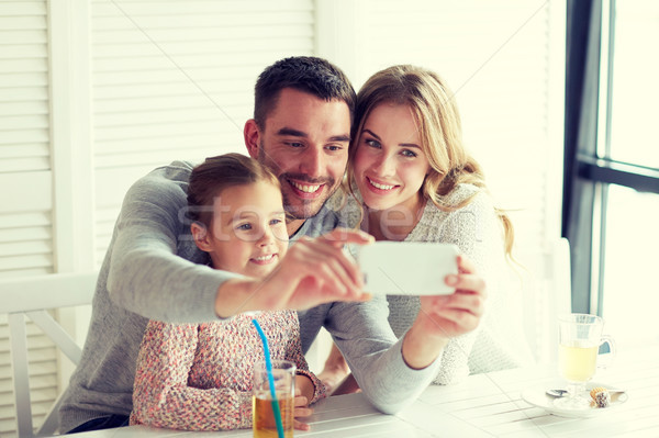 happy family taking selfie at restaurant Stock photo © dolgachov