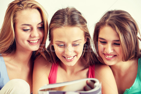 friends or teen girls reading magazine at home Stock photo © dolgachov