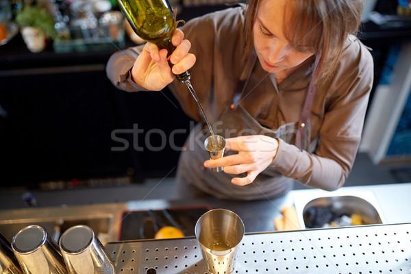 bartender pouring alcohol into jigger at bar Stock photo © dolgachov