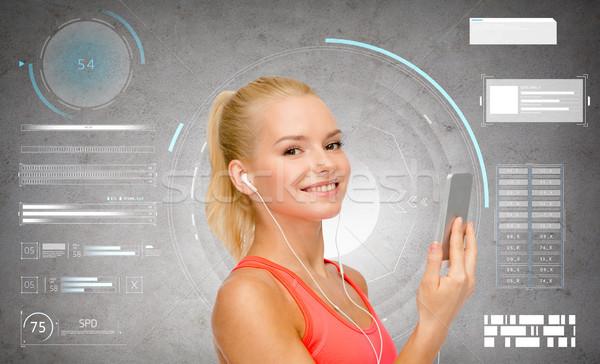Mosolyog sportos nő okostelefon fülhallgató sport Stock fotó © dolgachov