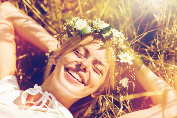 Stock photo: happy woman in wreath of flowers lying on straw
