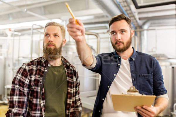 men with clipboard at craft brewery or beer plant Stock photo © dolgachov