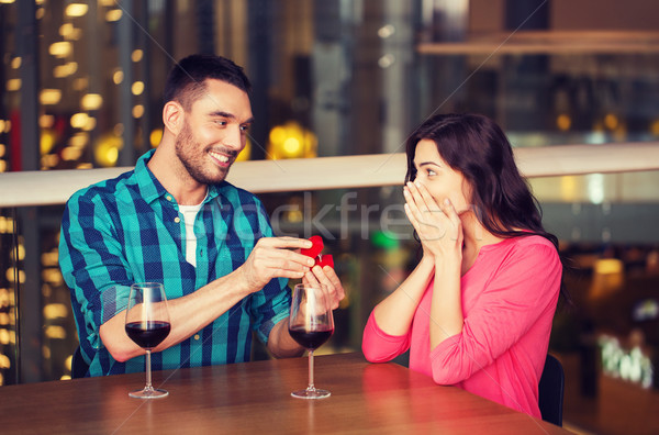 man giving engagement ring to woman at restaurant Stock photo © dolgachov
