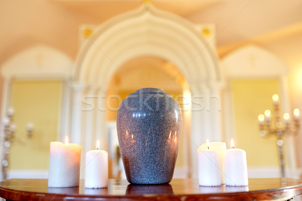 Stock photo: cremation urn and candles burning in church