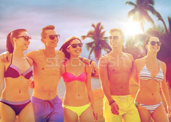 smiling friends in sunglasses on summer beach Stock photo © dolgachov