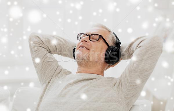 happy man in headphones listening to music Stock photo © dolgachov