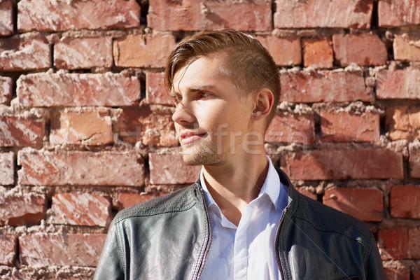 Retrato homem jaqueta de couro parede de tijolos estilo de vida pessoas Foto stock © dolgachov