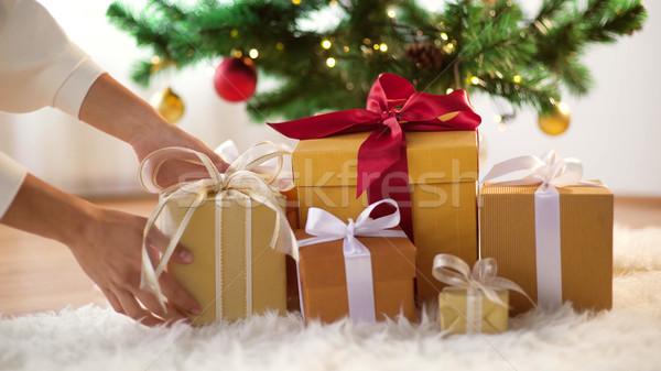 hands putting gift boxes under christmas tree Stock photo © dolgachov