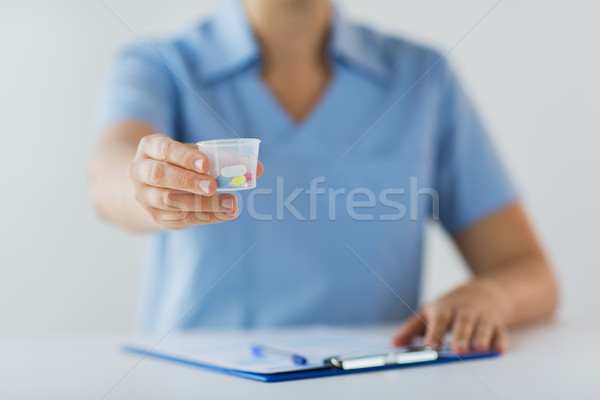 close up of doctor with pills in medical cup Stock photo © dolgachov