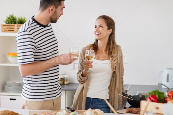 Stock photo: couple cooking food and drinking wine at home