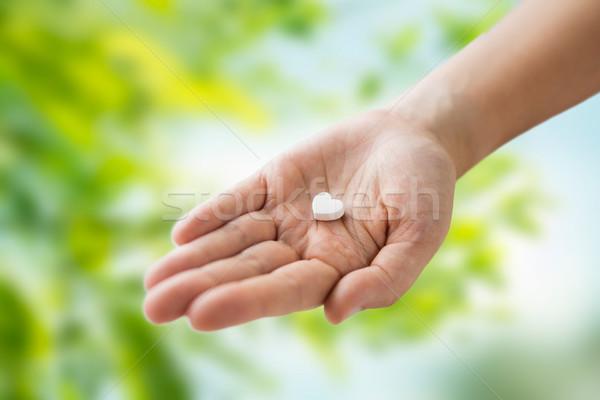 close up of hand holding medicine heart pill Stock photo © dolgachov