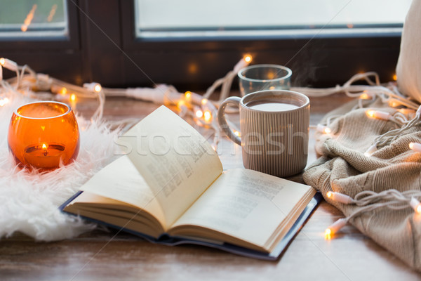 book and coffee or hot chocolate on window sill Stock photo © dolgachov