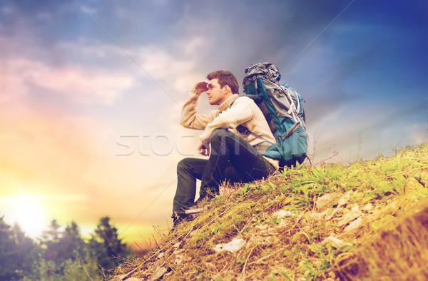 traveler with backpack hiking over sky background Stock photo © dolgachov