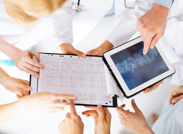 Stock photo: group of doctors looking at x-ray on tablet pc