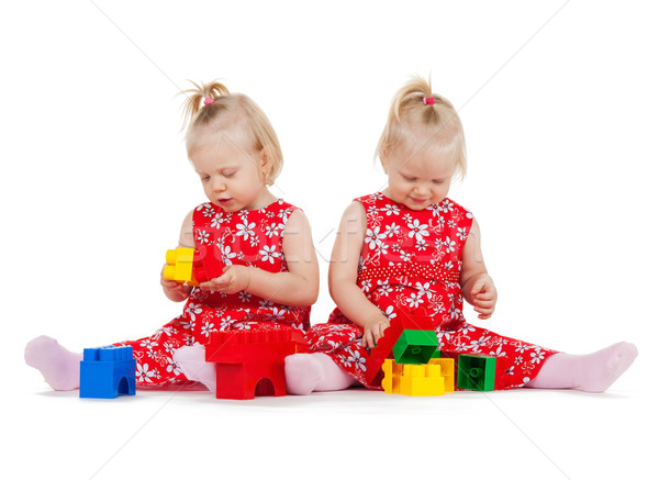 two twin girls in red dresses playing with blocks Stock photo © dolgachov