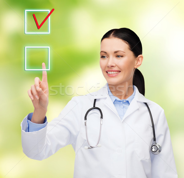 smiling female doctor pointing to checkbox Stock photo © dolgachov