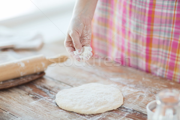 closeup of female hand sprinkling dough with flour Stock photo © dolgachov